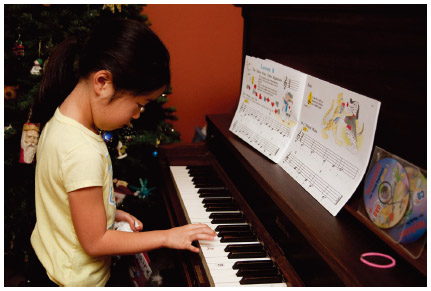 An 8-year-old Japanese American girl practices a piano lesson at home in Long Beach, California.