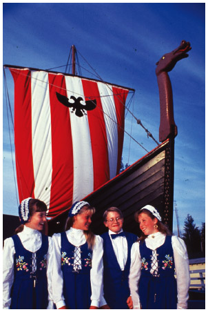 Norwegian Americans in traditional dress stand in front of a large replica of a Valhalia Viking ship, Alaska.