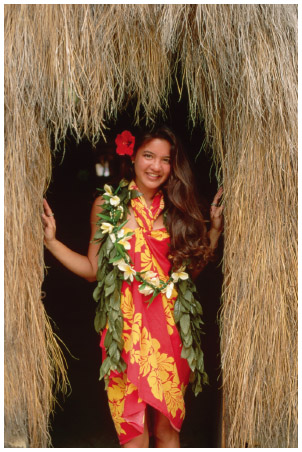 A Pacific Islander woman stands in the doorway of a traditional grass hut in a tourism photo.