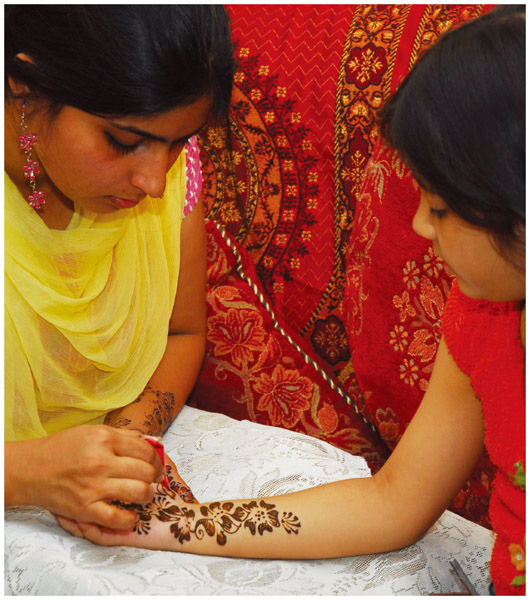 Pakistani American young women decorate their hands with Mehandi on the eve of Eid-ul-Fitr.