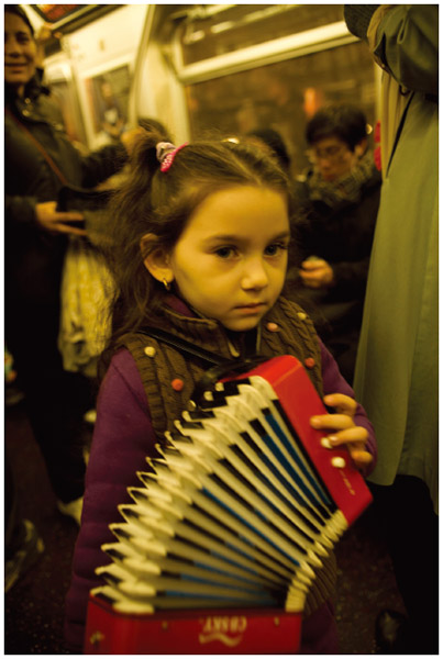 A Roma child plays accordian with her father on the New York City Subway.