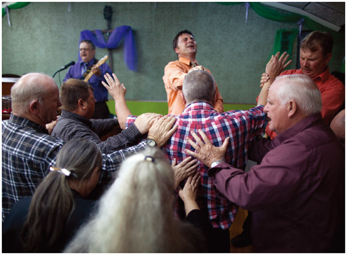 """The pastor and congregants lay their hands on a man during a service at the Church of the Lord Jesus in Jolo, West Virginia, in 2011. Rooted in Appalachian tradition and the New Testament Book of Mark, the """"Signs"""