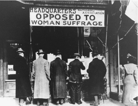 Men read literature posted in the window of the headquarters of the National Association Opposed to Woman Suffrage as a woman stands off to the side, New York, New York, 1910s.