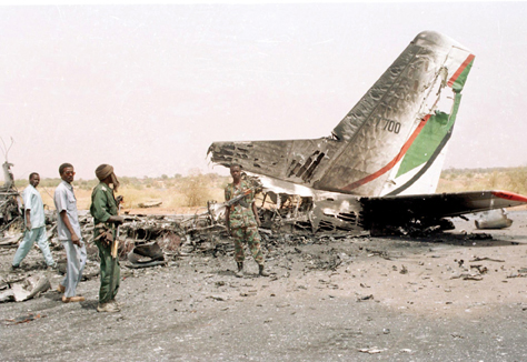 Sudanese soldiers look at a plane destroyed by members of the rebel Sudan Liberation Movement in Al-Fashir in April 2003, at the beginning of the Darfur Conflict.