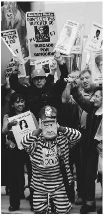 AT THE BOW STREET MAGISTRATE'S COURT IN LONDON, SCENE OF MUCH OF THE LEGAL DECISION-MAKING REGARDING THE FUTURE OF AUGUSTO PINOCHET, DEMONSTRATORS HOLD SIGNS AND A CARICATURE TO PROTEST THE POSSIBILITY THAT PINOCHET WOULD NOT FACE CHARGES FOR THE CRIMES HE MAY HAVE COMMITTED IN OFFICE. (AP/Wide World Photos. Reproduced by permission.)
