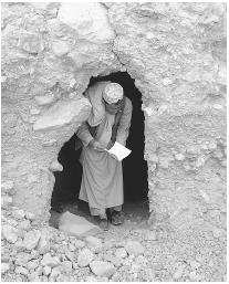 A MAN HOLDS SOME AL-QAEDA LITERATURE AS HE WALKS OUT OF A TUNNEL FROM A TERRORIST TRAINING CAMP IN AFGHANISTAN. A MANUAL WITH INSTRUCTIONS FOR THE SEPTEMBER 11 ATTACKS IN THE UNITED STATES WAS FOUND AMIDST THE BELONGINGS OF ONE OF THE ATTACKERS. (© AFP/CORBIS. Reproduced by permission.)