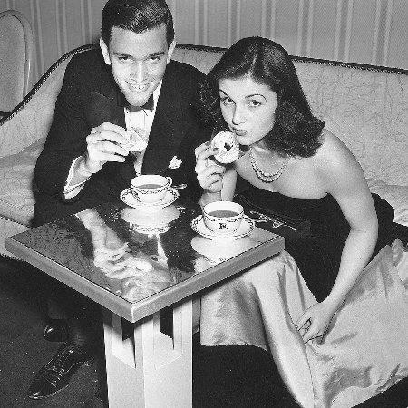 A dbutante and her escort enjoy a snack of doughnuts and coffee at a ball in the late 1930s. Despite the economic difficulties of the Depression, many of the very wealthy still maintained their lifestyles, which included attending lavish debuta