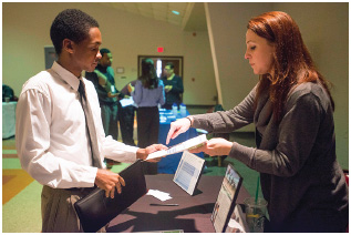 A job seeker gets information from a recruiter at a career fair in Columbus, Ohio.