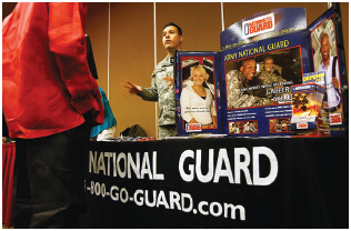 National Guard recruiter Sergeant Randy Martinez speaks to a potential soldier at a career fair in Denver, Colorado.