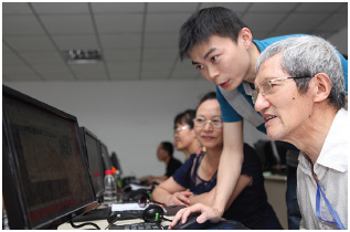 A student-volunteer teaches computer skills to older adults.
