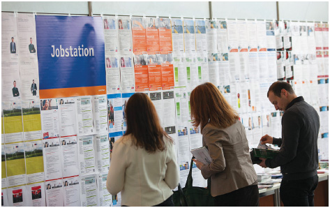 Students, graduates, and young professionals look at employment opportunities displayed on a job board at a job fair in Berlin, Germany.
