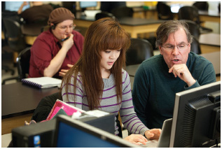 Michele Won works with professor Harold Riggs at Mass Bay Community College in a computer science course that is designed in conjunction with online learning from MIT. Students watch video lectures on their own through an edX MOOC (massive open
