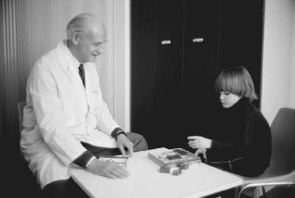 A doctor working with an autistic child