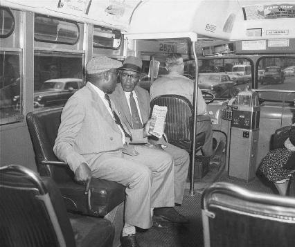 Two men ride in the first seat behind the driver of a city bus in Montgomery, Alabama, 1956