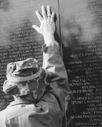 A Vietnam War veteran touches the engravings on the Vietnam War Memorial