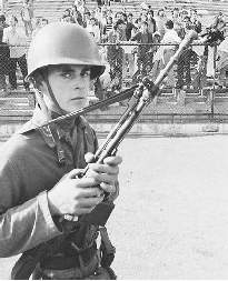 A Chilean Army soldier guards prisoners in Santiagos National Stadium, used as a detention center following the coup detat that overthrew Marxist president Salvador Allende.