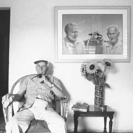 Gregorio Fuentes, a Cuban fisherman, was Hemingways inspiration for the title character of The Old Man and the Sea. With a portrait of Hemingway and Fuentes hanging in the background, this photograph was taken in 1994.