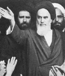 Ayatollah Khomeini, raising his hand to a crowd of supporters.