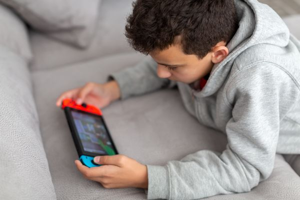 A boy lies on a sofa and plays a game on a Nintendo Switch.