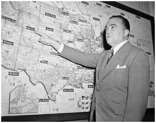 J. Edgar Hoover. FBI director J. Edgar Hoover reviews a map in his office locating the bureaus offices and operations across the United States in 1942.