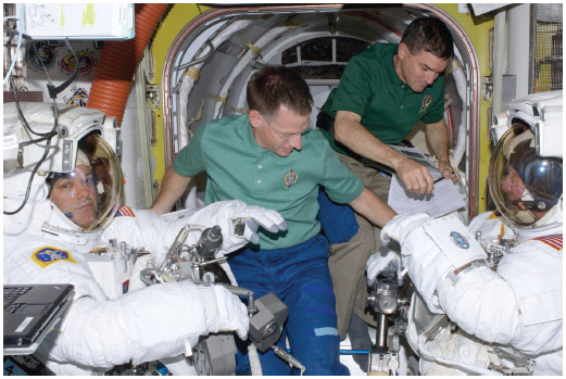 NASA astronauts aboard the International Space Station prepare for a space walk on July 12, 2011. From left to right they are Flight Engineer Mike Fossum, Shuttle Commander Chris Ferguson, Mission Specialist Rex Walheim, and Flight Engineer Ron