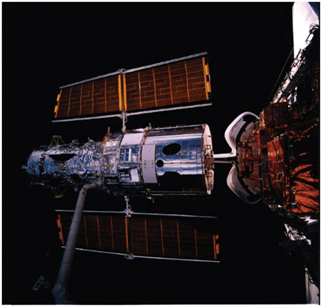 Solar power panels flare to the sides as the Hubble Space Telescope is lifted into position by the Remote Manipulator System from the cargo bay of the space shuttle Discovery.