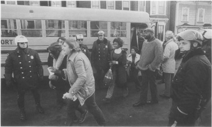 Police protect African-American students in the 1970s during a court-ordered desegregation campaign where students were bused to other districts to force a mix of races.