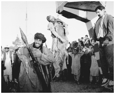 Taliban fighters greet each other in Kabul where the bodies of former Afghanistan President Najibullah and his brother Shahpur Ahmedzai hang. APWIDE WORLD PHOTOS
