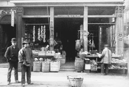 Chinese immigrants stand outside a butcher shop in Chinatown in San Francisco, California. © Bettmann/Corbis.