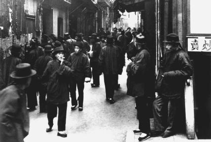 Pedestrians walk along the streets of Chinatown in San Francisco, California, in the early twentieth century. © Corbis.