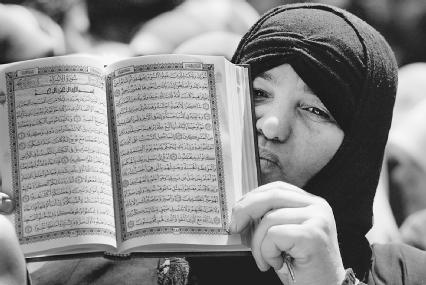 A Muslim woman holds up a copy of the Quran in Arabic. The Quran was revealed to the Prophet Muhammad by the angel Jabrail over a twenty-three year period in the seventh century.
