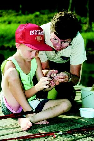Fresh-water education encompasses surface waters (e.g., lakes, ponds, streams, and wetlands) and groundwaters (e.g., cave, karst, and aquifer systems). Here a young angler learns from a park naturalist how to bait a hook.