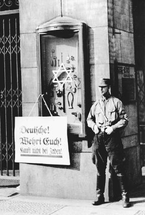 Storm troopers in front of a Jewish-owned shop with a sign encouraging Germans to boycott the store. (Reproduced by permission of the USHMM Photo Archives)