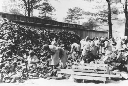 Women sort through a pile of shoes that had belonged to inmates killed at Auschwitz. (Reproduced by permission of the United States Holocaust Memorial Museum)