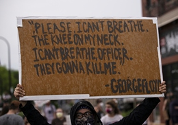 A Protester Holds a Sign Protesting Police Brutality in the Death of George Floyd