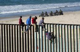 Central American Migrants Climb a Border Fence