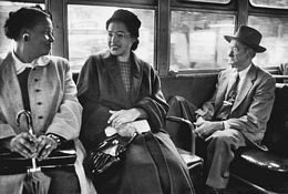 Rosa Parks (center) riding on a newly integrated bus in 1956. Parks sparked a 381-day boycott of...